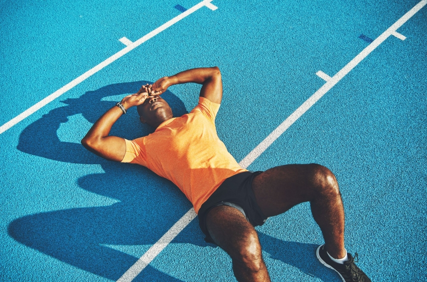 exhausted-young-athletic-lying-on-a-running-track-royalty-free-image-874030796-1543871922.jpg